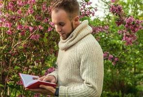 vriendelijke jongeman met rood boek in een zomertuin.