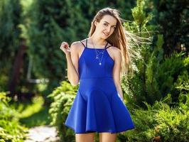 vrouw in modieuze blauwe jurk poseren in zomertuin.