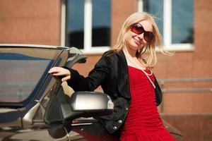 gelukkige jonge blonde vrouw bij de converteerbare auto foto