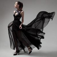 mode vrouw in fladderende zwarte jurk. grijze achtergrond.