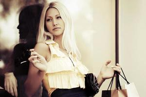 jonge mode vrouw met boodschappentassen bij het raam van het winkelcentrum foto