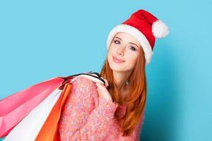 roodharige meisje met boodschappentassen op blauwe achtergrond.