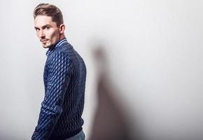 elegante jonge knappe man in stijlvolle donkerblauwe jas.