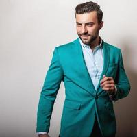 elegante jonge knappe man in stijlvolle turquoise jas.