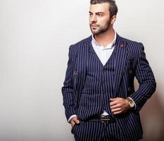 elegante jonge knappe man in klassiek donkerblauw kostuum. foto