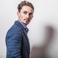 elegante jonge knappe man in stijlvolle blauwe jas. foto