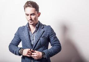 elegante jonge knappe man in stijlvolle blauwe jas.
