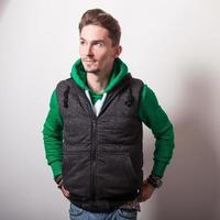 aantrekkelijke jonge man in grijs vest en groene trui.