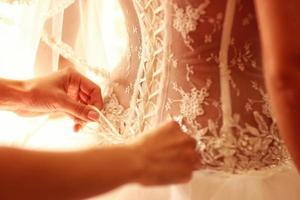 bruidsmeisje met knopen van de bruidsjurk foto