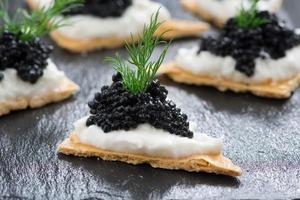 crackers met roomkaas en zwarte kaviaar foto