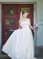 mooie rode haren bruid poseren met bloemen buiten. europese bruiloft.
