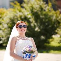 mooie rode haren bruid poseren met bloemen buiten.