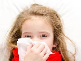 klein meisje liggend in het bed en haar neus snuiten foto