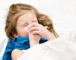 klein meisje haar neus snuiten foto