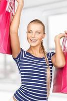 gelukkige jonge vrouw met boodschappentassen foto
