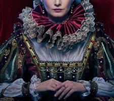 koningin in koninklijke jurk en weelderige kraag foto