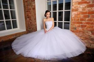 mooie bruid zitten poseren in haar trouwjurk. studio. foto