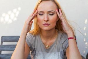 blond haar meisje zitten en lijden als gevolg van hoofdpijn. foto