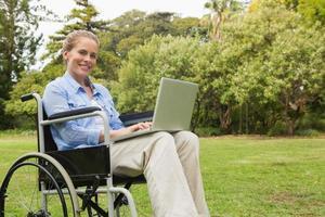 glimlachende vrouw in een rolstoel met laptop foto