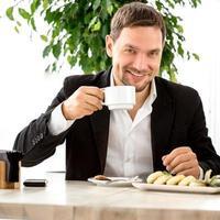 knappe man koffie drinken in het restaurant foto