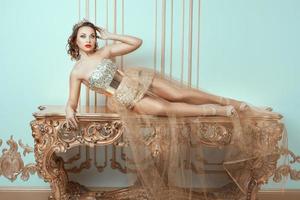 modieuze vrouw ligt op een dure antieke tafel. foto