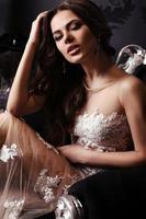 prachtige vrouw in elegante jurk poseren in luxe interieur