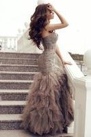 sensuele vrouw met lang donker haar in luxe jurk met lovertjes