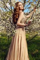 sensuele vrouw met lang rood haar in luxe jurk met lovertjes