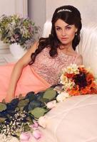 mooie bruid met donker haar poseren met boeket bloemen