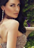 vrouw met donker haar in luxe jurk met lovertjes en bijou,