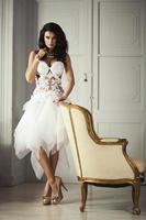 mooie volwassen vrouw met mode kapsel en witte fauteuil poses foto