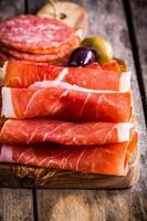 dunne plakjes prosciutto met salami op een snijplank foto