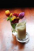 houten tafel met bloemen en kaars foto