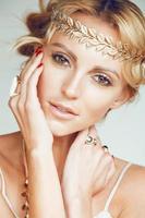 jonge blonde vrouw gekleed als oude Griekse godin, gouden sieraden foto