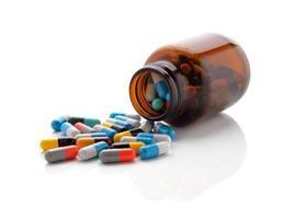 pillen uit fles op witte achtergrond foto
