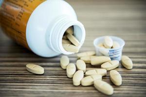 bruine pillen een pil fles op tafel. vintage toon. foto