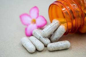 kruidencapsules die uit een fles morsen. foto