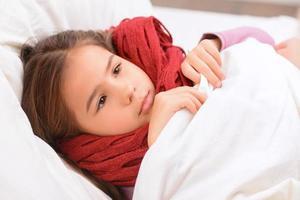 klein meisje liggend in bed foto