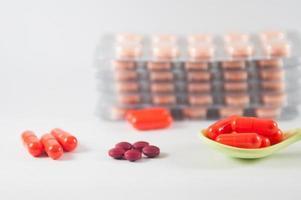 oranje capsule in lepel op blisterverpakking achtergrond foto
