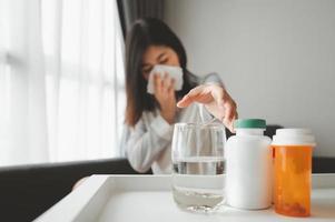 zieke Aziatische vrouw die naar medicijnen reikt foto