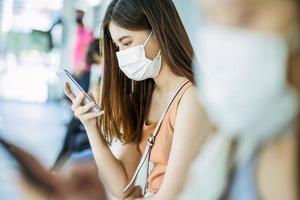 Aziatische vrouw passagier met masker te wachten op het station foto