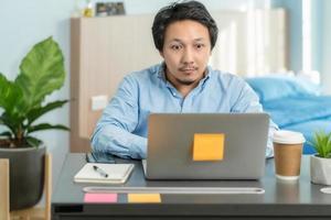 Aziatische zakenman met behulp van technologie thuis kantoor foto