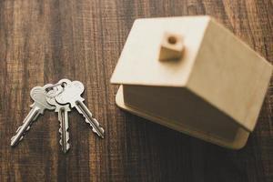 bovenaanzicht van houten huis en sleutels foto