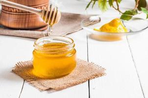 honingpot met lepel en citroen stroomt, houten achtergrond foto