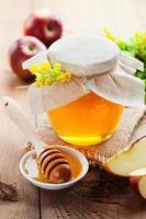 pot met honing en houten stok foto