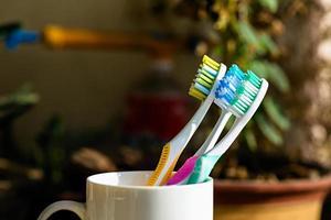 drie tandenborstels op een beker foto