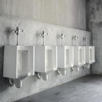 lijn van wit porseleinen urinoirs in openbare toiletten foto