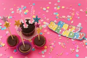cupcakes op roze confetti achtergrond - gelukkige verjaardagskaart foto
