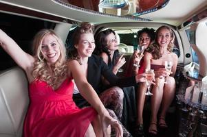 vijf meisjes in een limo die drinken en feesten foto