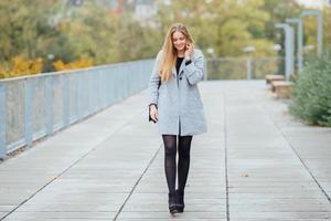 blonde haren vrouw lopen op straat en glimlach foto